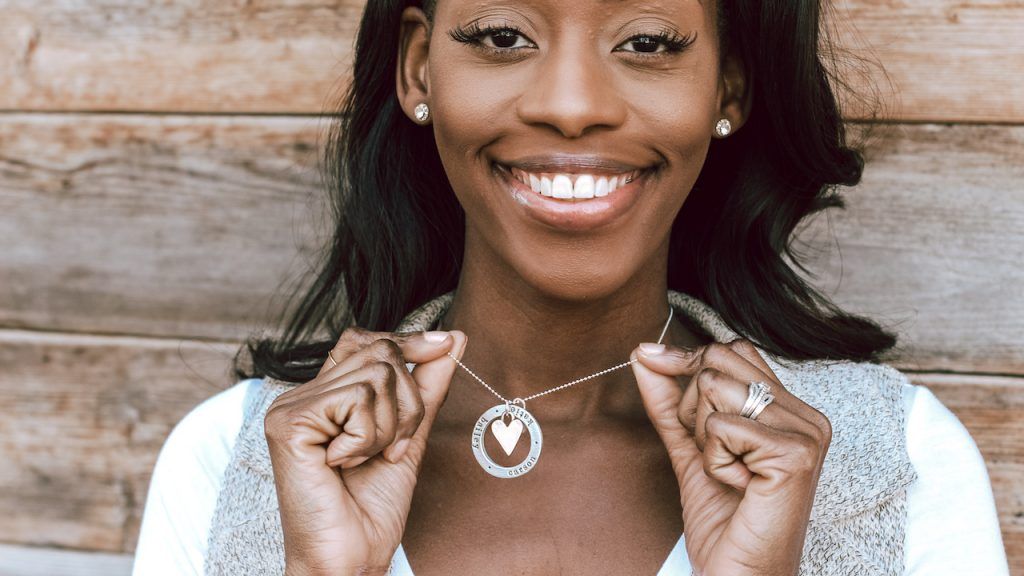 Model wearing jewelry for moms with children's names and a heart charm
